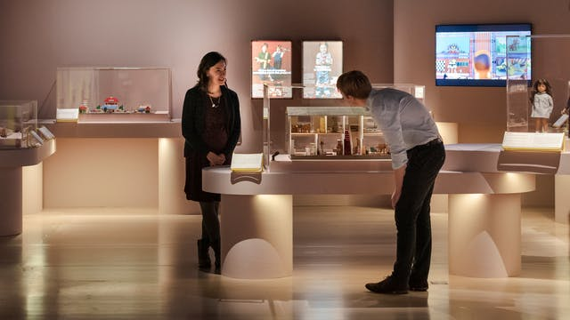 Visitors at the Play Well exhibition at Wellcome Collection. Two people are looking at items in a case.