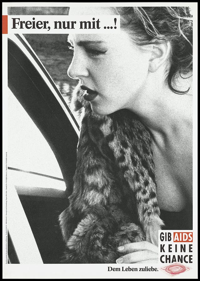 A black and white close up picture of a woman leaning into a car window wearing a leopard print fur coat.