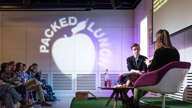 Photograph of two women having a conversation on a small stage. In the background are the audience. Projected onto the far wall is the silhouette of an apple with the words Packed Lunch circling the top of the apple.