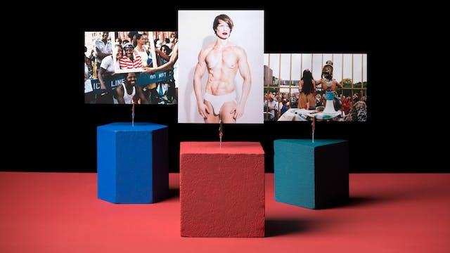 拿着在一台红色桌面上的三个形状的照片在有鳄鱼夹的一台红色桌面。红色的立方体拿着一个主要赤裸裸的人的肖像象,红色唇膏和白色丁字裤。Teal Triangle正在举行一张表演的图片,其中两个人,一个男人和一个女人,在寻址一群人时,他们的背部是在镜头上的服装。一只蓝色的六角形正在拿着一群站在'不要交叉'屏障的人群的照片。人群的情绪很欢乐。两名妇女正在与相机蒙上灿烂的笑容,虽然另一个人在他们面前举行。相框也在第四个人的头上休息。