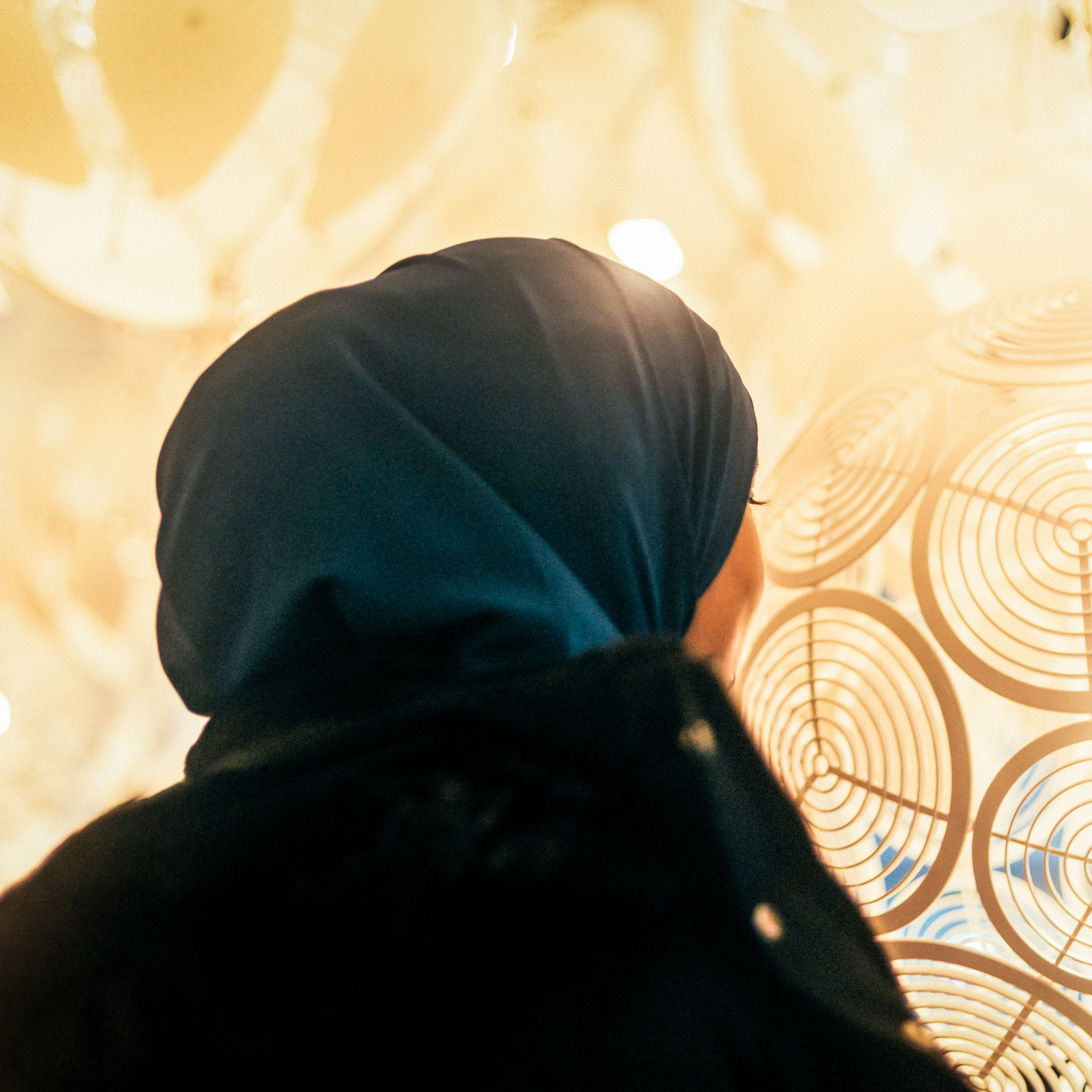 Photograph of a woman wearing a blue head scarf facing away from the camera. The viewpoint is low down looking up at her. In the background is the warm yellow and orange colours of patterned lamp shades in a shop display.