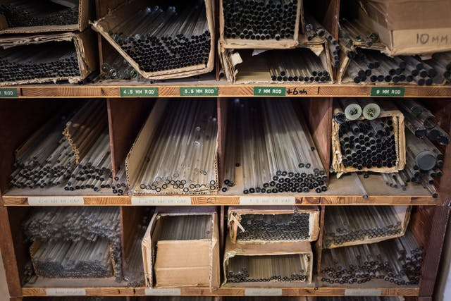 Wooden pigeon-holes filled with glass tubes of varying sizes and thicknesses.