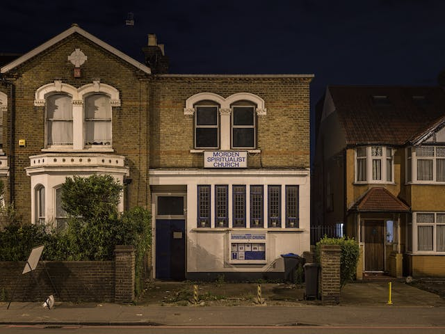 Photograph of Morden spiritualist church at night.  The building is uncharacteristic of typical church architecture, and appears to be from the Edwardian period.  The bottom half of the building is rendered white, whilst the top half is bare brick.  On the ground floor, the blue door is offset to the left with six tall long windows to the right. A sign with blue letters on white spells