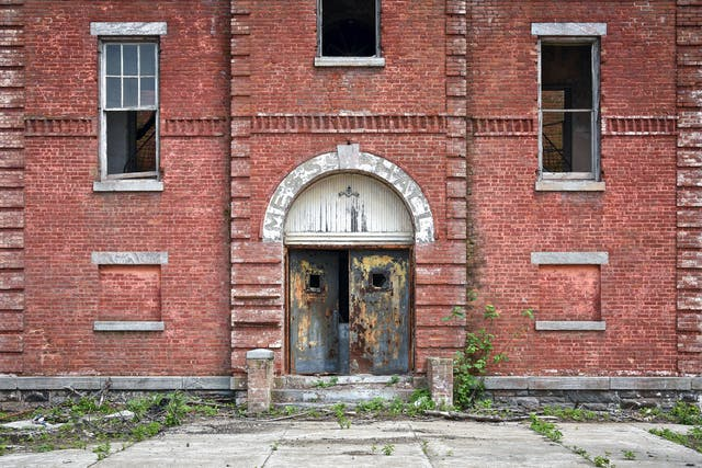 Photograph of the front of an abandoned red brick building, which fills the frame. In the centre is the main door which is slightly ajar. Above the door are the faded letters which spell out
