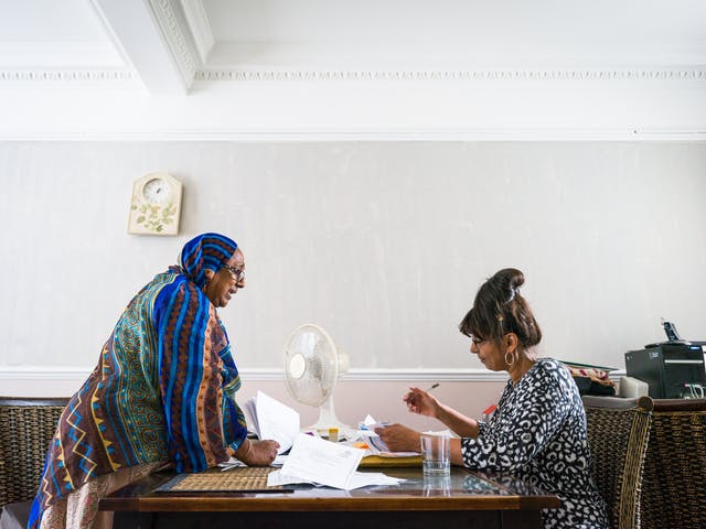 Photograph of Sarifa Patel with her personal assistant working at a table in her living room.