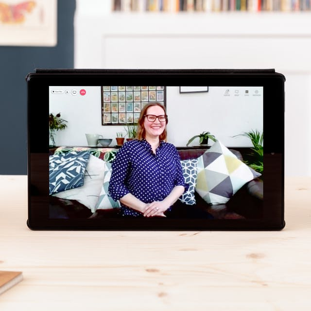 Photograph of a tablet on a desk. On screen is a live event with the speaker Katherine Rawling. There is a red telephone icon in the top left-hand corner of the screen. The speaker has shoulder length light brown hair and is wearing a blue top, they are sitting on a sofa. There is a shelf with houseplants on it in the background. Around the tablet is a pot of pens, a notebook and a succulent in a pot.