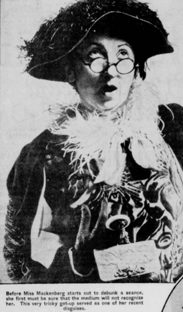 Black and white photo of a woman with a surprised expression wearing a hat and fancy scarf.