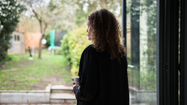 Photograph of a woman standing next to a set of bifold doors looking out into a domestic garden. The left profile of her face can been seen looking into the distance. She is holding a mug.