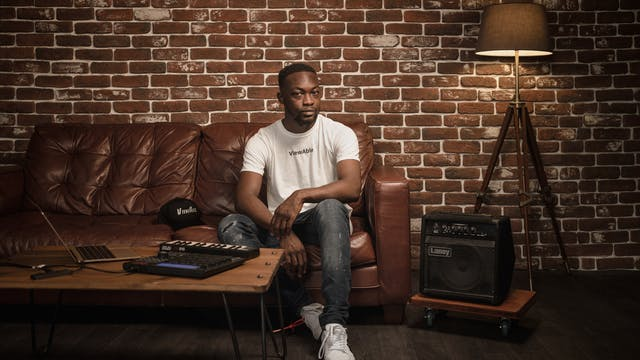 Photographic full length portrait of a man in a white t-shirt sitting on a leather sofa. In front of him to the left of the frame is a wooden table with a laptop, keyboard and beat-box. To the right of the frame is a bass speaker and a floor standing lamp.  Beside him on the sofa is a hat. A single line of text is legible on both the T-shirt and hat, reading