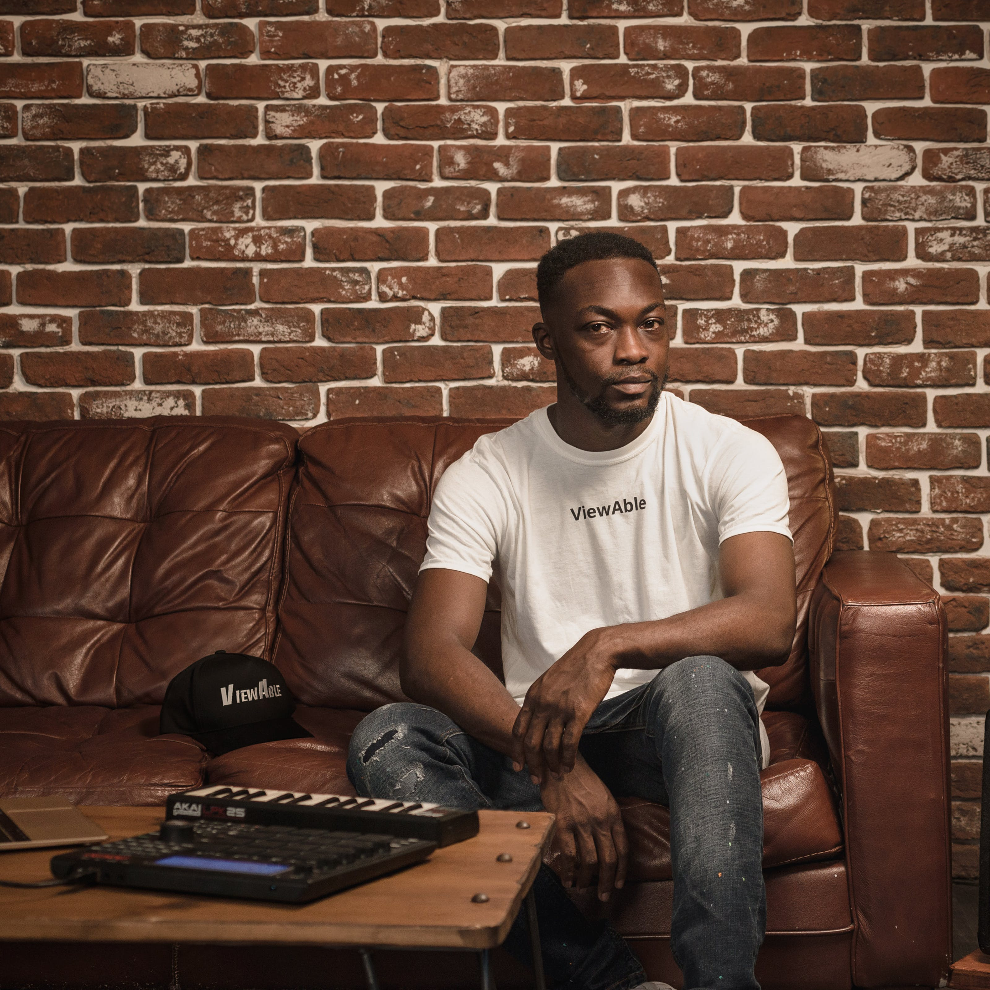 Photographic full length portrait of a man in a white t-shirt sitting on a leather sofa. In front of him to the left of the frame is a wooden table with a laptop, keyboard and beat-box. To the right of the frame is a bass speaker and a floor standing lamp.  Beside him on the sofa is a hat. A single line of text is legible on both the T-shirt and hat, reading 'Viewable'.