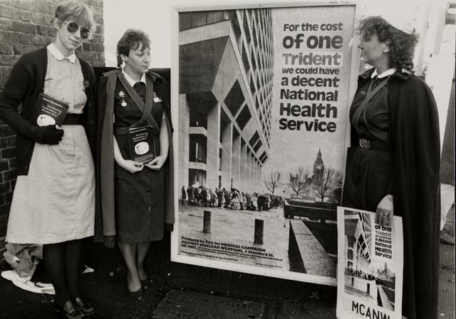 "Black and white photograph of three nurses in uniform protesting about spending money on nuclear weapons rather than healthcare. They stand either side of a poster that reads ""For the cost of one Trident we could have a decent National Health Service."""