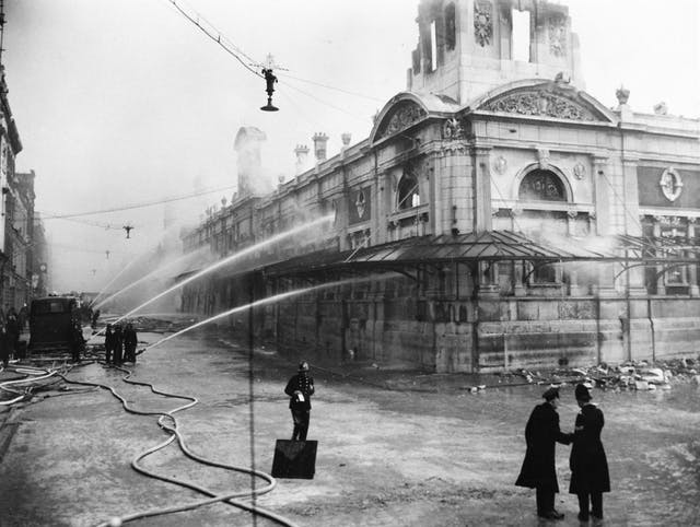 Black and white photograph showing water jetting out of hose pipes onto a market building. Police and fire crew in the foreground.