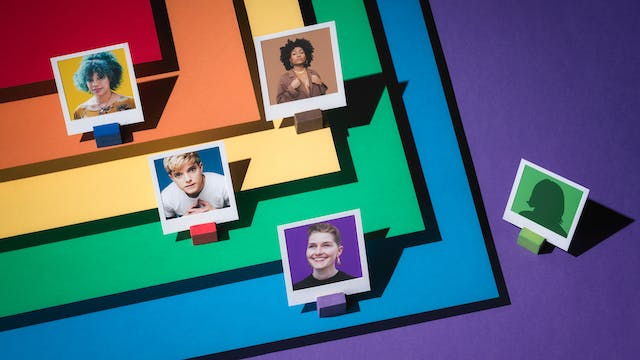 Photograph of four portraits featuring LGBTQ+ comedians, framed within a white paper frames.  To the right of the image, an anonymous figure is also framed within a white frame. Layered beneath them in tiers are the LGBTQ+ colours of red, orange, yellow, green blue and purple; which forms the floor of the set.  The colours are laid out in such a way as they form a chevron.