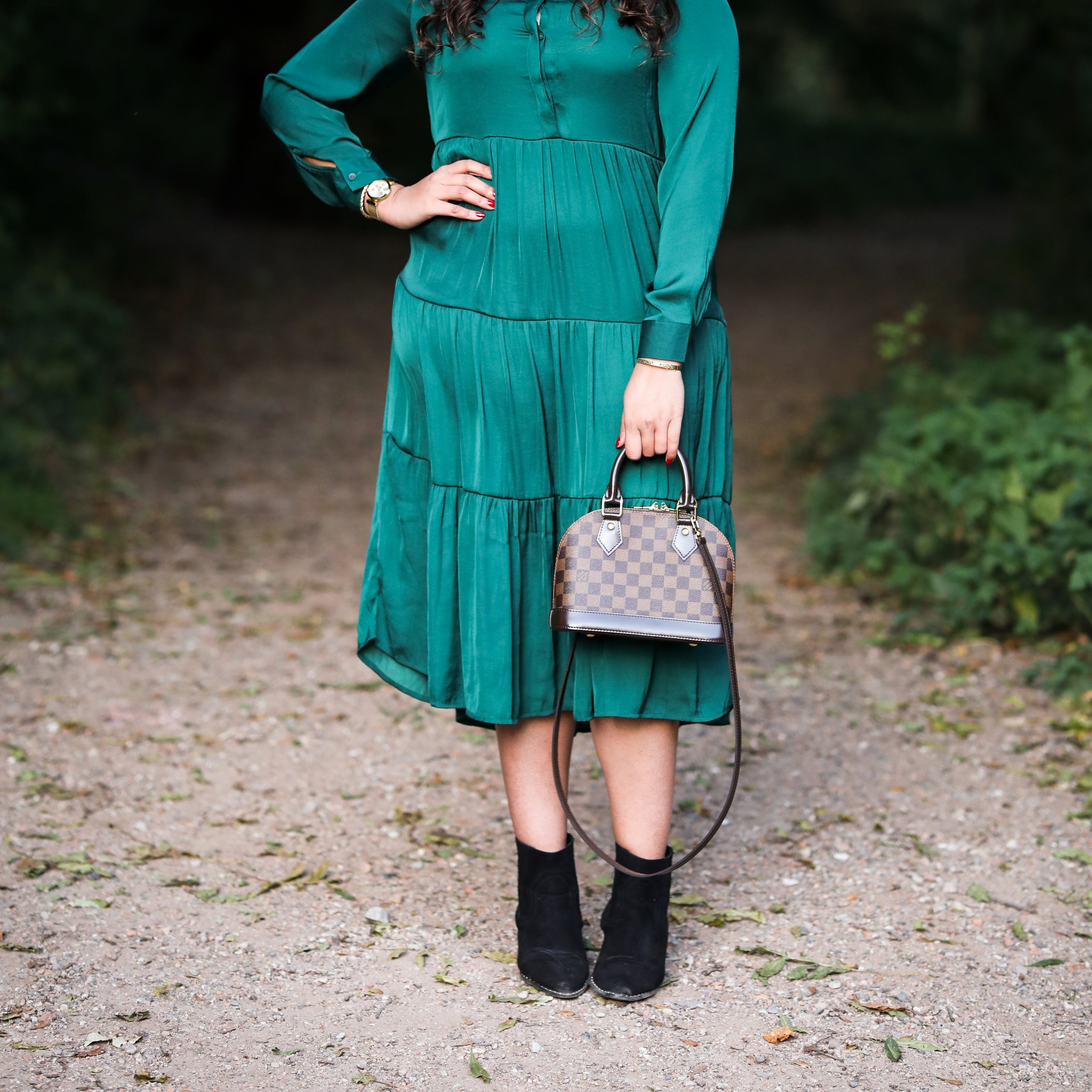 Photograph of a woman from her shoulders to her feet, wearing an emerald green dress with a shiny lustre. She is standing with her right hand on her hip and in her left hand she is holding a small hand bag in front of her left leg. In the background can be seen a park or woodland scene with a footpath disappearing into the distance. On either side of the path is green vegetation.