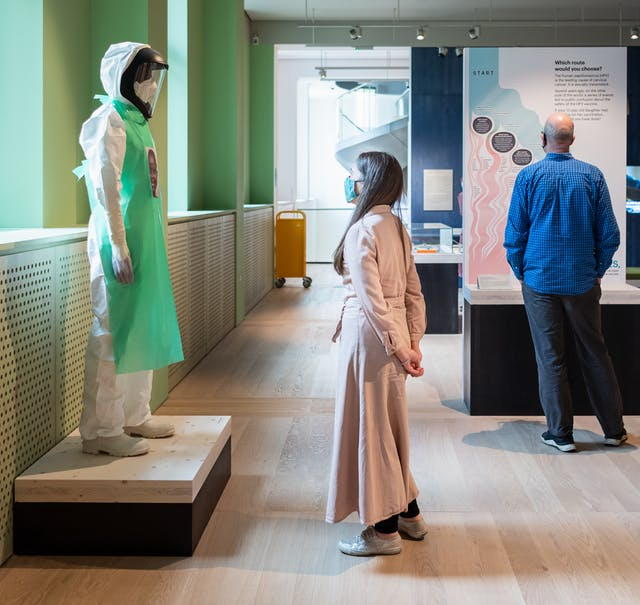 A photograph showing a visitor looking at an exhibition exhibit of a mannequin wearing a white hazmat suit, visor and green apron standing on a low wooden platform. On the green apron there is a portrait of the carer that would have been wearing the suit whilst treating Ebola patients. To the right is the back of another visitor who is looking at a different exhibit.