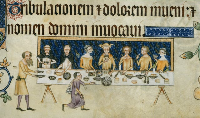 An illustrated manuscript showing nine figures gathered around a dining table laden with food and dishes.