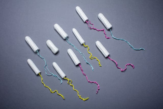 Photograph of 10 unwrapped tampons arranged in a diagonal pattern on a blue background. The yellow, pink and blue cords are trailed behind each tampon except for one.