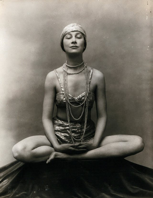 A woman in 1920s dres seated in the Buddha Pose