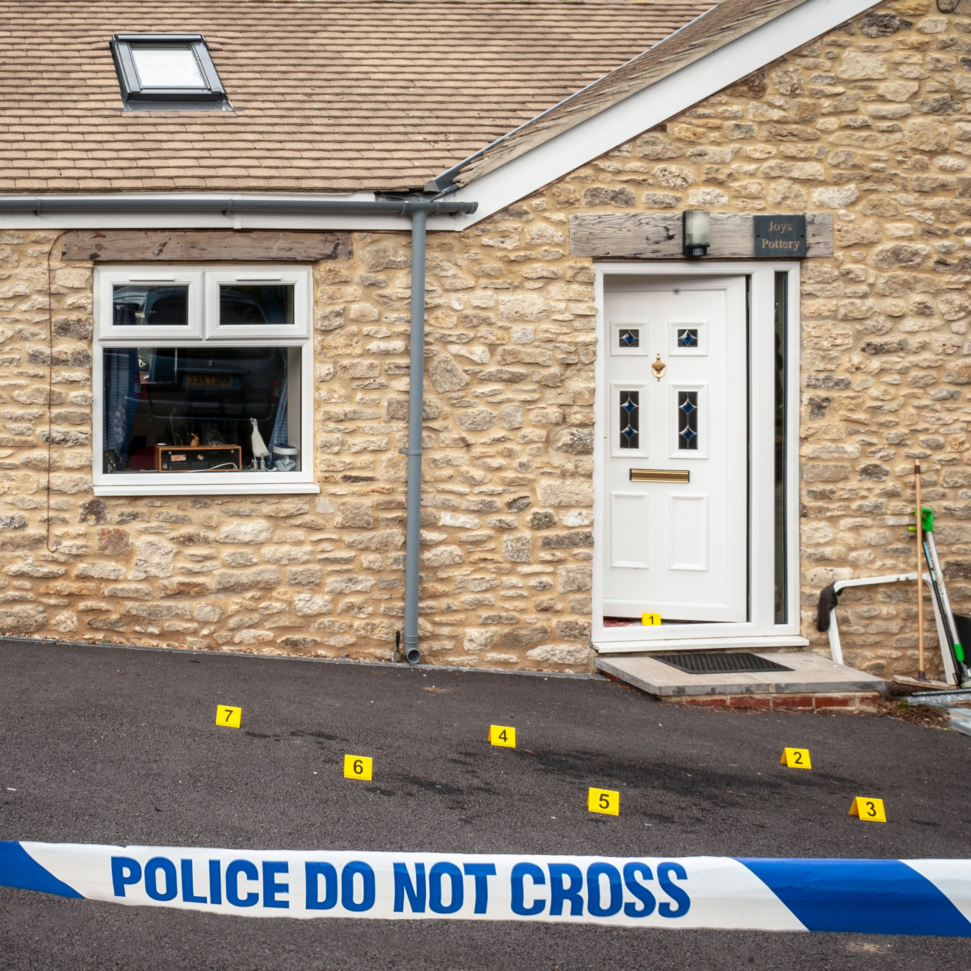 Photograph of the front of a house with the front door slightly open and forensic crime scene numbered yellow markers on the ground. In the foreground is a police cordon with 'Police Do Not Cross' written across the tape.