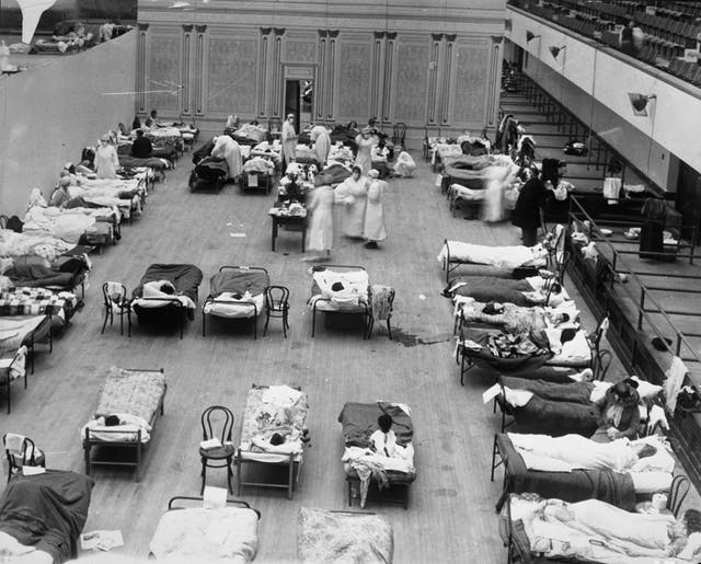 The photograph depicts volunteer nurses from the American Red Cross tending influenza sufferers in the Oakland Auditorium, Oakland, California, during the influenza pandemic of 1918.