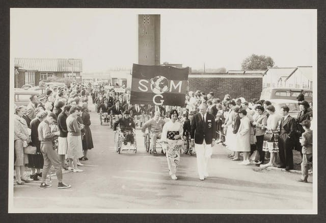 Black and white photographic print of a parade. A woman in a kimono and a man in a dark blazer and white trousers lead the parade, and behind them follow row upon row of people in wheelchairs wearing tracksuits or suits. The front row of people in wheelchairs carries a banner that says SMG with a globe above the letter G. The street is lined with people in 1950s clothing, who watch the parading athletes. One man in the front left of the photograph is wearing a tracksuit and Converse sneakers and is taking photographs.