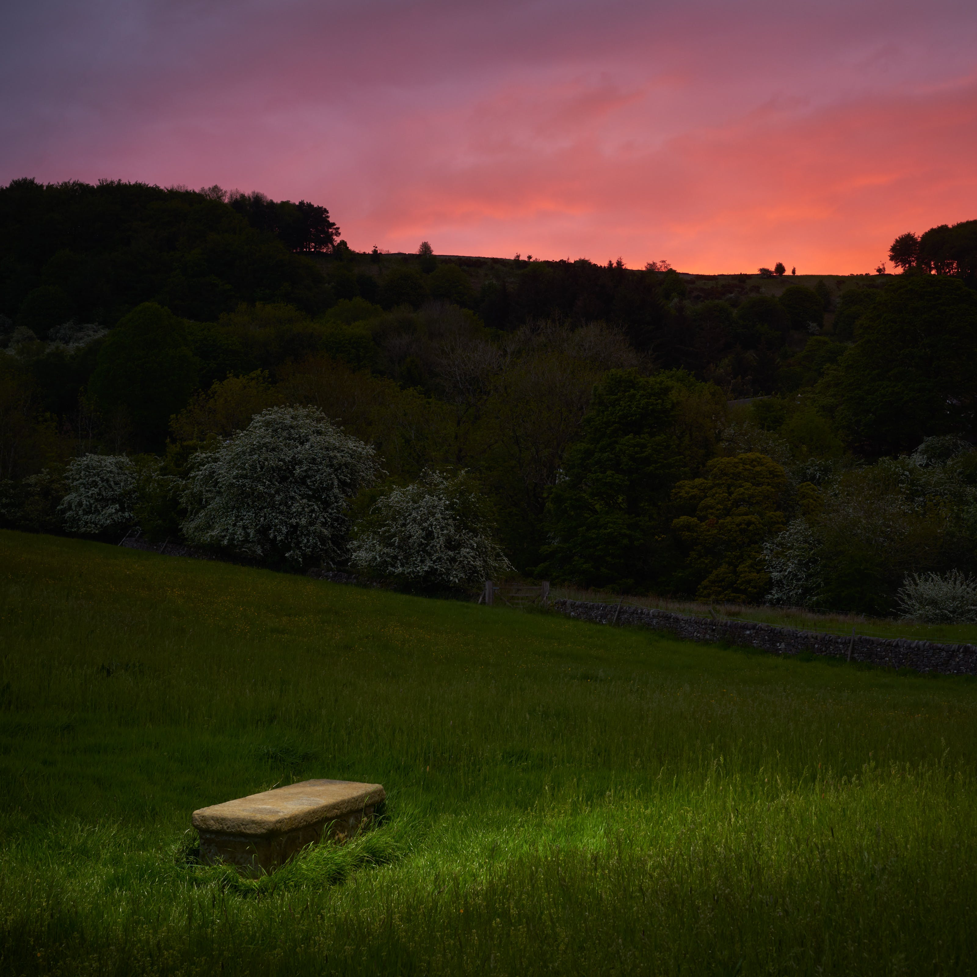 Photograph of a rural landscape at dusk. In the background is a dramatic red sky. In the foreground is a spotlit plain stone grave.