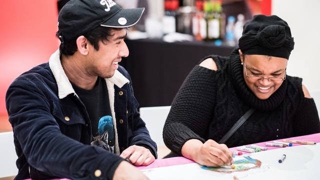 A photograph of two people sitting at a table drawing on a large white sheet of paper with colourful crayons.