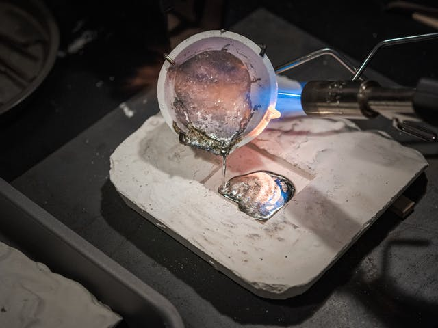 Photograph of molten lead being poured into from the ceramic heating container into the plaster mould.  A flame burner appears to the right, applying a continuous source of heat to the lead.