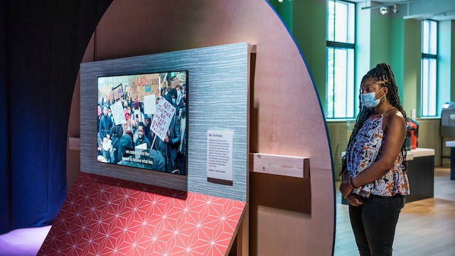 Photograph of a young woman wearing a face covering exploring an exhibition gallery space. The woman is standing to the right of frame, arms clasped across her body, reading an information panel on the front of a large circular wooden board. This text is hidden from view as the camera is looking at the back of this wooden board. Behind the board is a large TV screen mounted to a vertical rectangular board wich is covered in a blue patterned upper section and a re patterned lower section. On the screen is a still from a video showing a demonstration or protest with people carrying banner. One of the banners has the words,