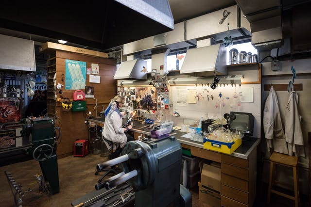 Picture of a workshop with various pieces of equipment, large items in the foreground and many small items on a bench in the background. Under an extraction hood, a woman in a white coat sits in front of a blowtorch working glass.