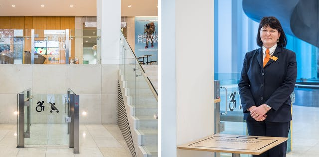 A diptych. The photograph to the left shows the inside of the entrance to the Wellcome Collection with an open air lift with a glass push-button door for wheelchair and pushchair access.  Alongside this is a short staircase, both of which take you up to the atrium visible above where further lifts, a spiral staircase, a cafe, and a bookshop are located. The photograph on the right shows a member of security staff standing behind a small table for bag checks to take place.