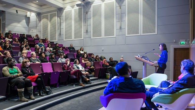 Colour photograph of people sitting in the Henry Wellcome Auditorium at Wellcome Collection on purple flip-down seats. They look towards a woman standing at a podium speaking and gesturing.