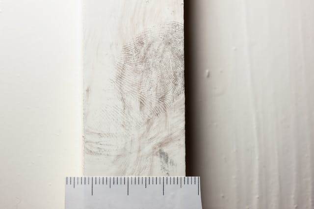 Photograph of a dusted fingerprint on a white door frame with a ruler scale beneath.