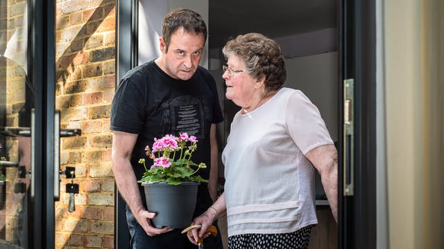 Photograph of a man and his mother stood side by side in a patio doorway. The man wearing a black t-shirt and blue trousers standing on the left is holding a plant pot containing a pink flowering plant. He is looking to camera with a long suffering look on his face. His mother, standing on the right, is wearing a pink blouse and blue patterned skirt and is looking towards him, her face in profile. Her right hand is holding the handle of her walking stick. To the left of them can be seen the patio doors with a bunch of keys in the lock and the brick wall of the back of the house. To the right of them is a section of the door frame.