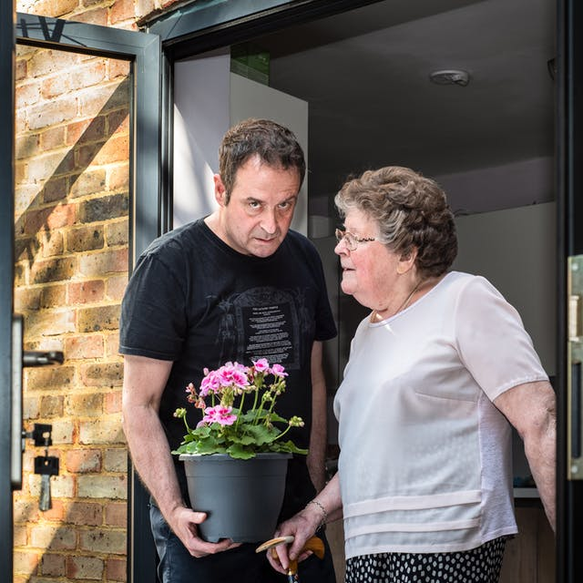 一个男人和他的母亲的照片在一个露台门道入口并排站立。穿着黑色t恤和蓝色长裤站在左边的男人拿着一个植物罐,包含粉红色的开花植物。他正在望着相机,脸上脸色长痛苦。他的母亲,站在右边,穿着一件粉红色的衬衫和蓝色图案裙子,正在朝着他,她的脸在档案中。她的右手握着她的手杖。他们的左侧可以看到露台的门,锁在锁和房子后面的砖墙中。它们的右侧是门框的一部分。
