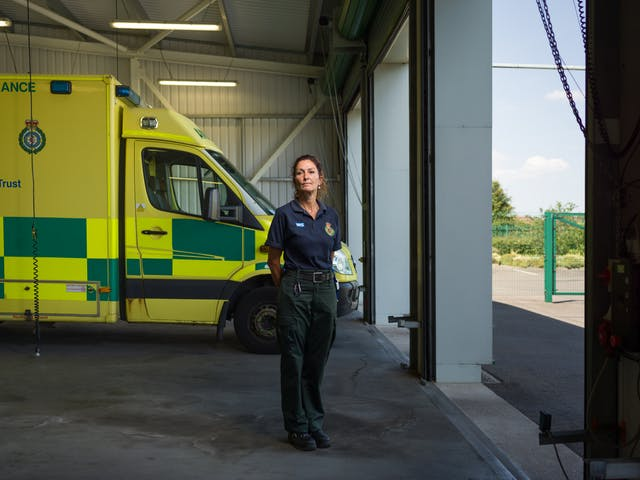 Photographic full length portrait of Mandy English, a paramedic, in her ambulance station.