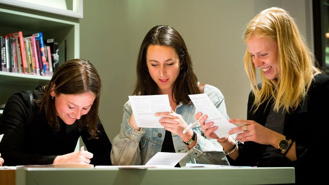 Image of three women looking at paper and writing