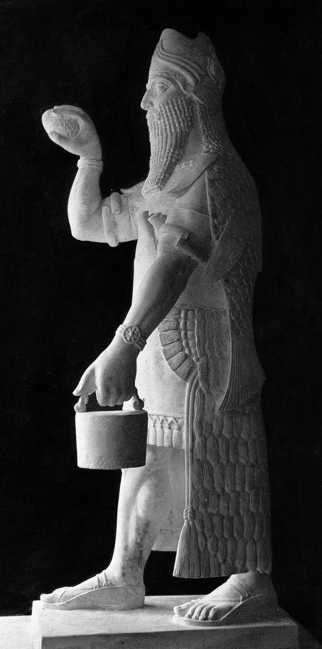 Black and white photograph of a statue depicting a man wearing sandals and a cloak that has a fish-scale texture. He is holding some sort of bucket.