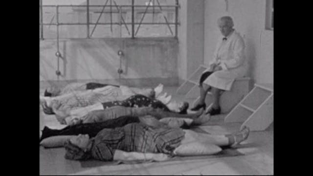 Image of women lying on their backs in a line. A man wearing a doctor
