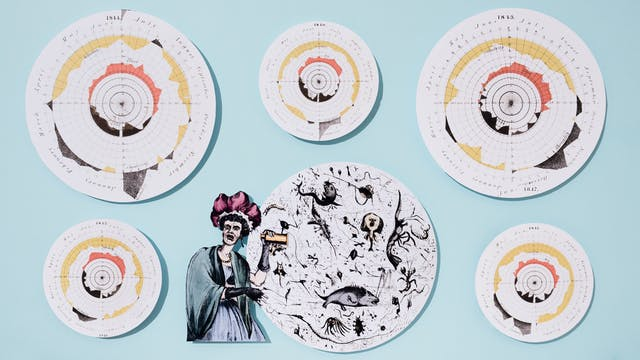 Photograph of cut out pieces of archive material from above, all raised slightly above a flat light blue background. One of the illustrations shows a shocked woman looking at enlarged microscope illustration of caricatured microbes found the dirty water causing a cholera outbreak. Surrounding the woman is a series of circular illustrations showing infection rates of the cholera outbreak during different years starting in 1840.