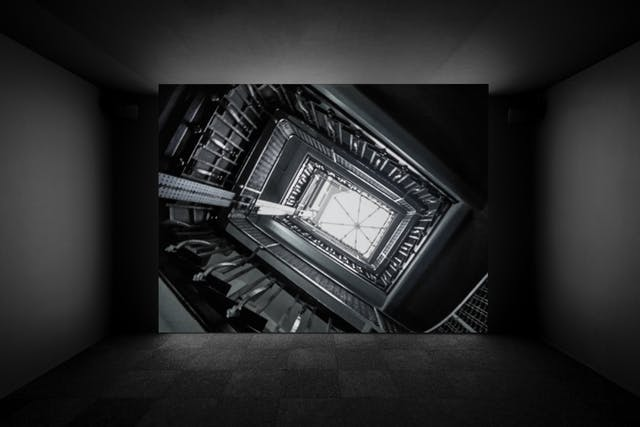Photograph of a projector screen showing a film installation as part of the exhibition, Living with Buildings at Wellcome Collection