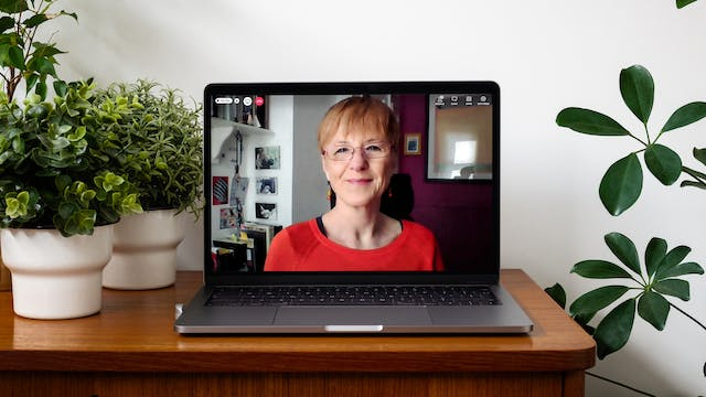 Photograph of a laptop on a desk. On the laptop screen is a live event showing the speaker, Wendy Moore with a red telephone icon in the top left-hand corner of the screen. She has short light brown hair and glasses. She is wearing a red top, sitting in an office chair in her home with pictures on the wall behind her, a bookshelf and postcards stuck on the wall. The laptop is sitting on a wooden desk with houseplants around it.