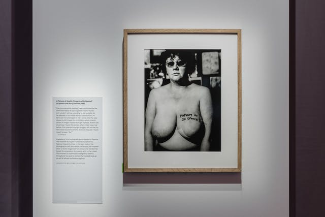 Photograph of a wall in a gallery showing a framed black and white photograph of a woman, naked from the waist up. On her left breast is written the words,