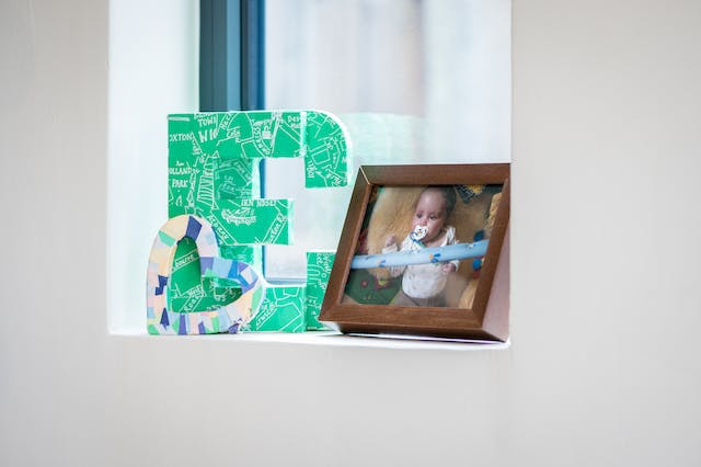 Photograph showing a window recess containing an ornamental letter E and C, and a small heart shape. There is also a framed photograph of a baby lying on the floor.
