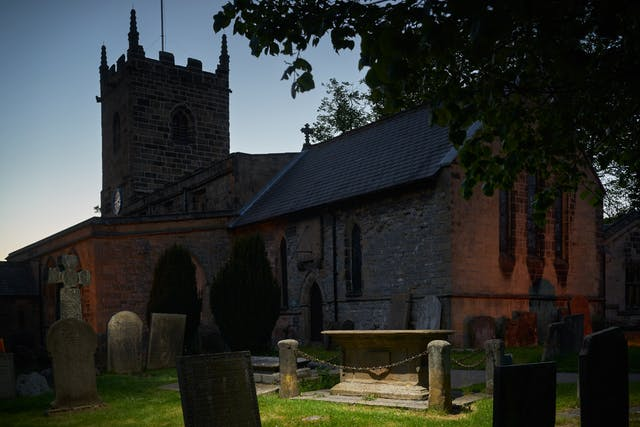 Photograph of a church and church yard at dusk. in the foreground the grave of Catherine Mompesson, wife of the rector, is spotlit.
