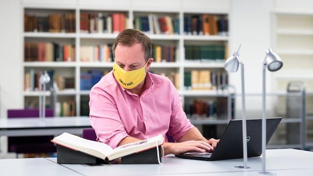 穿一件桃红色衬衣和一张黄色面孔覆盖物的一个人的照片坐在图书馆里的一张桌上。他的手在膝上型计算机的键盘上摔跤,他看着一本打开的书,在书架里休息。在他身后的距离后面,可以看到书架和其他桌子。