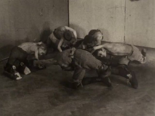 Black and white still from a film showing boys crawling around in a circle on the floor, arching their arms over their heads as if swimming.