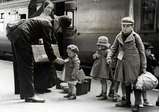 Children stand on a station platform, with labels attached to their coats.