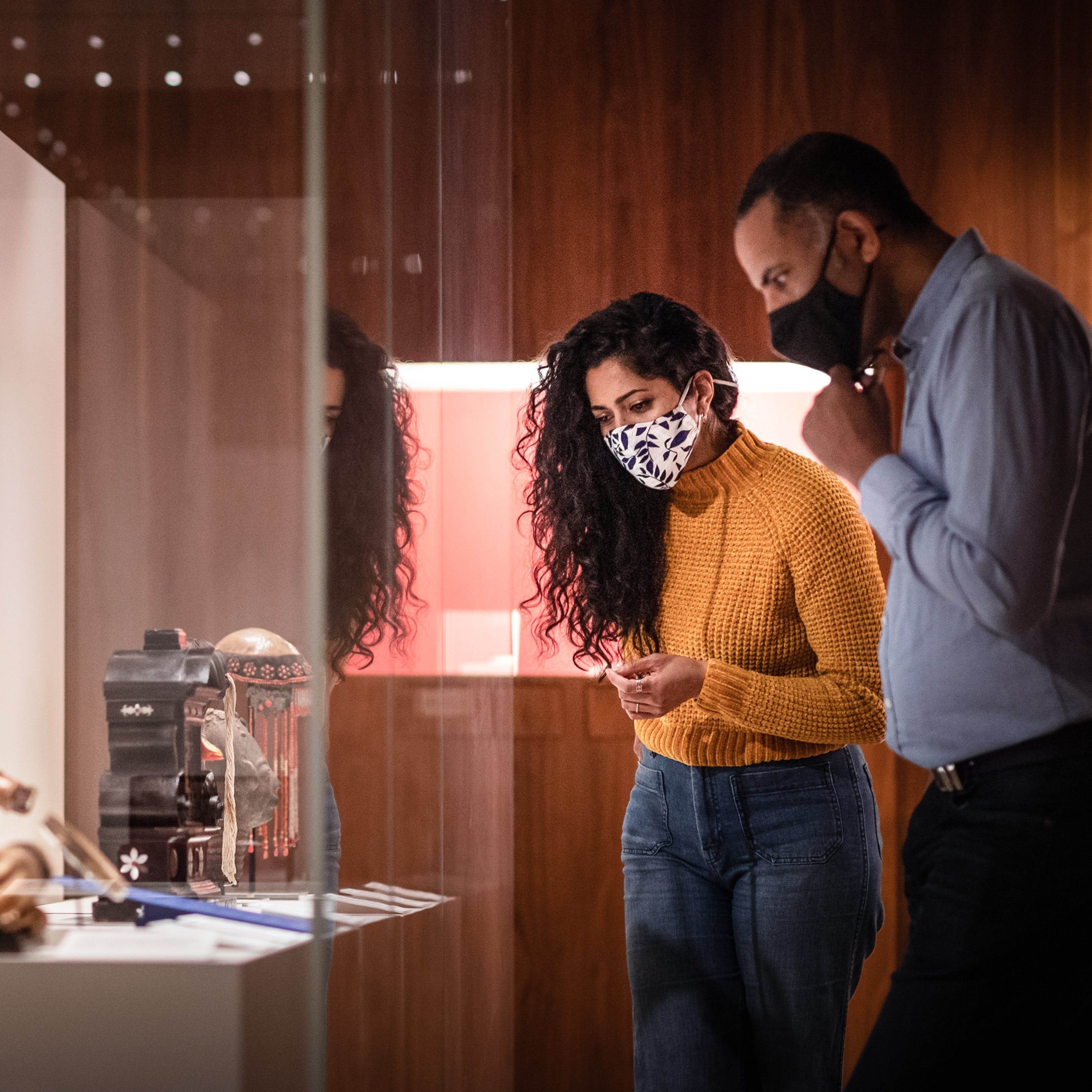 Photograph of a man and a woman wearing face coverings exploring a museum gallery. The woman is wearing a yellow knitted jumper and a pair of blue jeans. The man is wearing a blue shirt and dark trousers. It is a dark gallery with spot lit exhibits and wooden panelled walls. The couple are standing side by side to the right of the frame in mid discussion about objects in a display case. To the left of the frame is the large glass display case they are looking at, containing several objects, from vases to models of the human head to small cabinets.