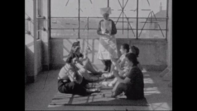 Image of women sitting down in two lines, facing each other. A nurse stands in the middle of them.
